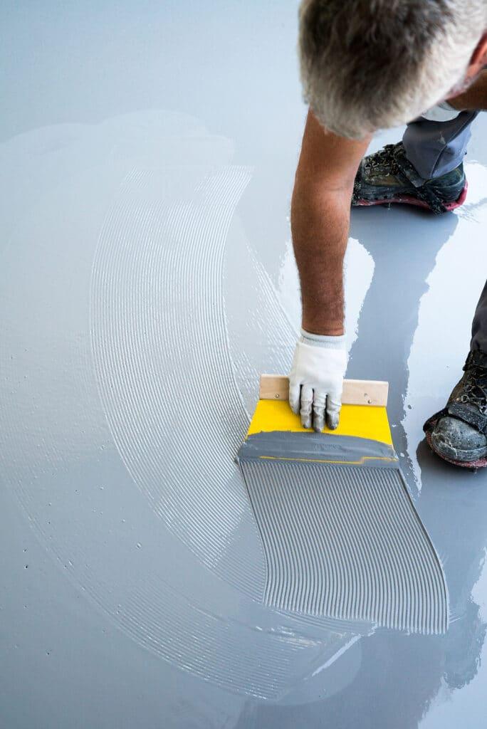 Construction worker spreading resin flooring
