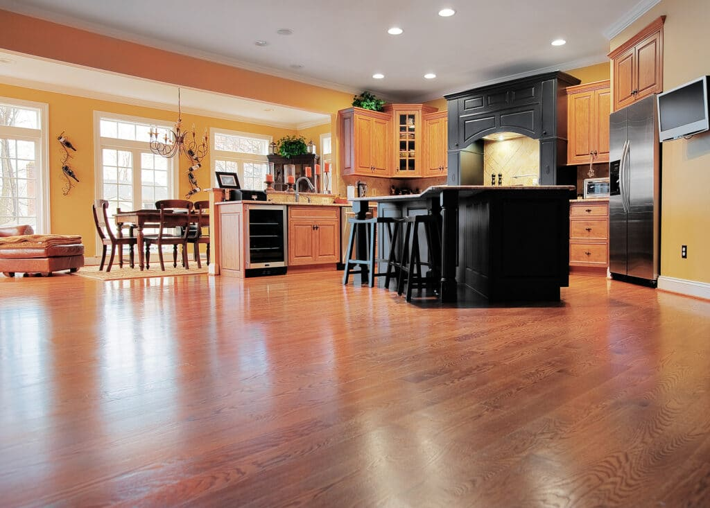 A large expanse of wood flooring in a kitchen and dining room